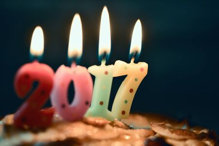 sweet seventeen: closeup of four lit number-shaped candles of different colors forming the number 2017, as the new year, on a cake