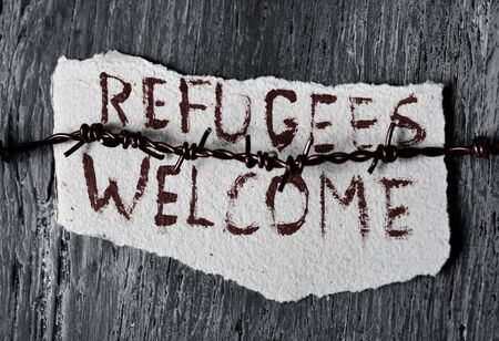displaced: closeup of a barbed wire and a piece of paper with the text refugees welcome handwritten in it on a rustic wooden surface Stock Photo