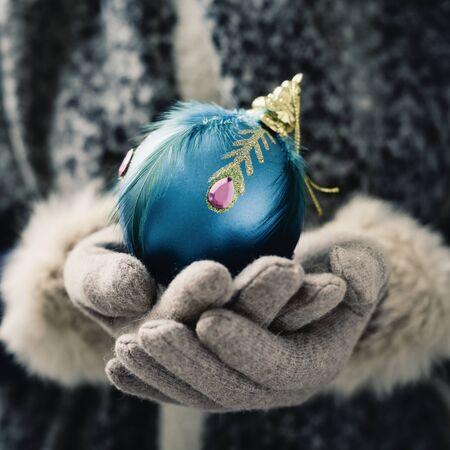 navidad elegante: Primer plano de una mujer caucásica que llevaba un par de guantes elegantes que sostiene una bola de Navidad azul elegante en sus manos