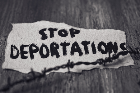 displaced: closeup of a barbed wire and a piece of paper with the text stop deportations handwritten in it on a rustic wooden surface