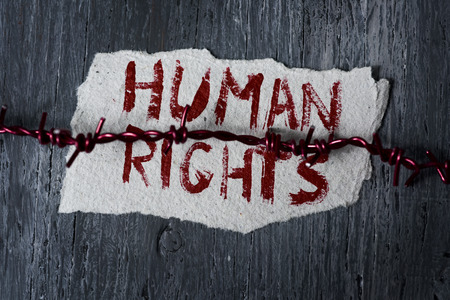 captives: high-angle shot of a barbed wire and a piece of paper with the text human rights handwritten in it on a rustic wooden surface Stock Photo