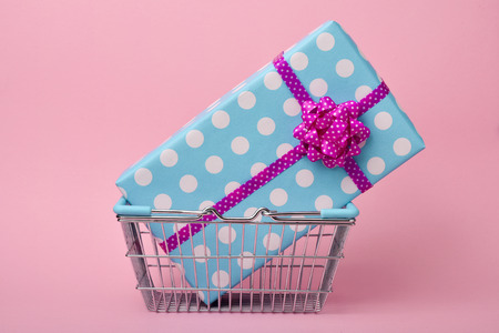compulsive shopping: closeup of shopping basket with a gift wrapped in a blue paper patterned with white dots and tied with a pink ribbon, on a pink background