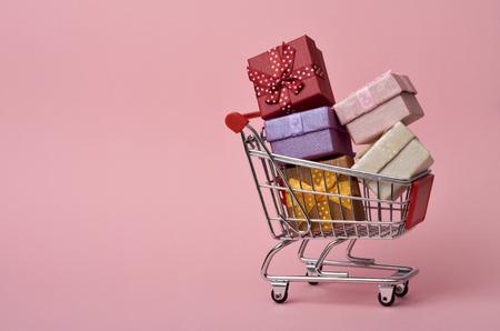 een winkelwagentje vol met geschenken van verschillende kleuren op een roze achtergrond, met een negatieve ruimte