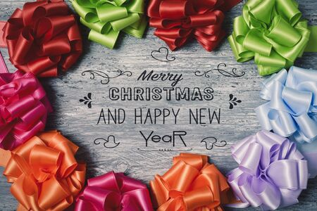 loopy: some satin gift ribbon bows of different colors forming a circle on a rustic wooden surface and the text text merry christmas and happy new year in the center