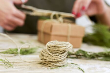 paperboard: closeup of a young caucasian woman with her fingernails painted red tying a jute string around a brown paperboard gift box, on a rustic wooden surface full of natural twigs and branches