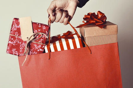 closeup of the hand of a young caucasian woman with her fingernails painted red holding a red shopping bag full of gifts wrapped in different papers Stock Photo