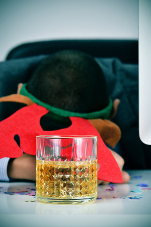 drinks after work: closeup of a young caucasian businessman wearing a reindeer antler headband sleeping at his desk, covered with confetti and with a glass of liquor in the foreground, after an office christmas party