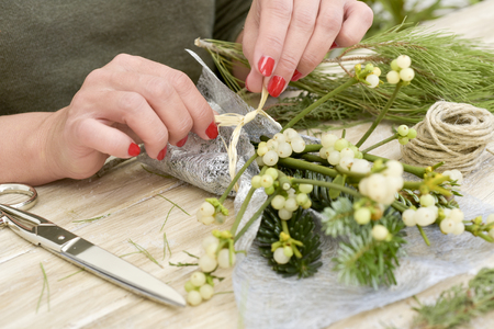 closeup of a young caucasian woman with her fingernails painted red arranging a bunch of mistletoe wrapped in a silvery fabric, on a rustic wooden surface Stock Photo