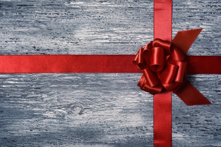 loopy: a crossed red satin ribbon tied in a gift bow on a gray rustic wooden surface, with some negative spaces