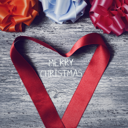 loopy: some satin gift ribbon bows of different colors and a red satin ribbon forming a heart on a rustic wooden surface and the text merry christmas in the center Stock Photo