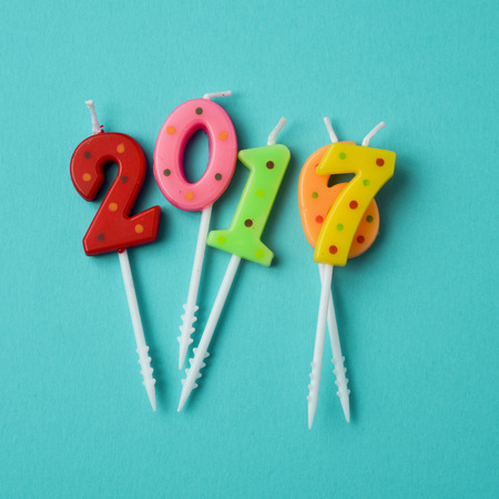 high-angle shot of some number-shaped candles of different colors forming the number 2017 and the number 2016, as the new year and the old year, on a blue background