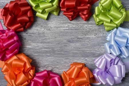loopy: some satin gift ribbon bows of different colors on a rustic wooden surface forming a circle with a negative space in the center