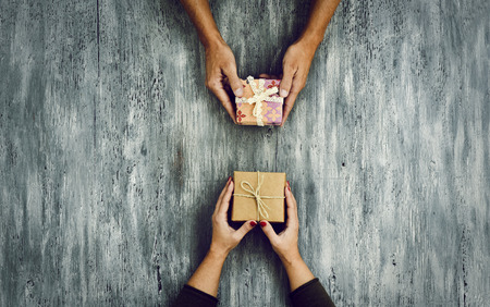 high-angle shot of a young caucasian woman and a young caucasian man exchanging gifts on a rustic wooden table, with some negative spaces around them Archivio Fotografico