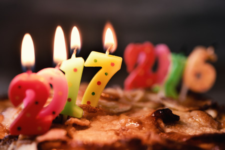 sixteen year old: four lit number-shaped candles of different colors forming the number 2017, as the new year, on a cake, and more burn-out and melted candles forming the number 2016, as the old year, in the background