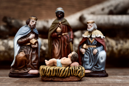 closeup of the three kings carrying their gifts adoring the Child Jesus on a rustic scene Banque d'images