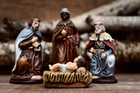 Primer plano de los tres reyes que llevaban sus regalos que adora al niño Jesús en una escena rústica