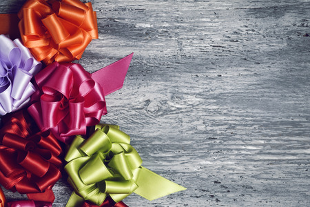 loopy: some satin gift ribbon bows of different colors on a rustic wooden surface, with a negative space