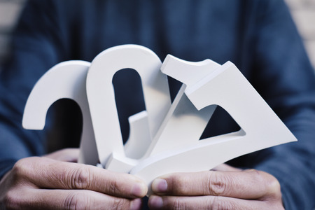 0 1 year: closeup of a young man holding some white numbers forming the number 2017, as the new year, in front of him Stock Photo