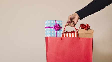 merchandise: closeup of a young caucasian woman with her fingernails painted red holding a red shopping bag full of gifts wrapped in different papers against an off-white background, and a negative space