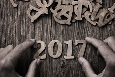closeup of a young man forming the number 2017, as the new year, with wooden numbers, on a rustic wooden table, in sepia toning