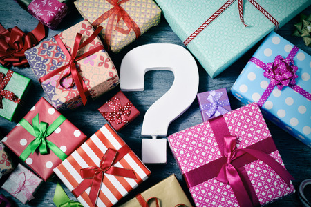 high-angle shot of many gifts wrapped in nice papers and tied with ribbons of different colors and a white three-dimensional question tag in the center