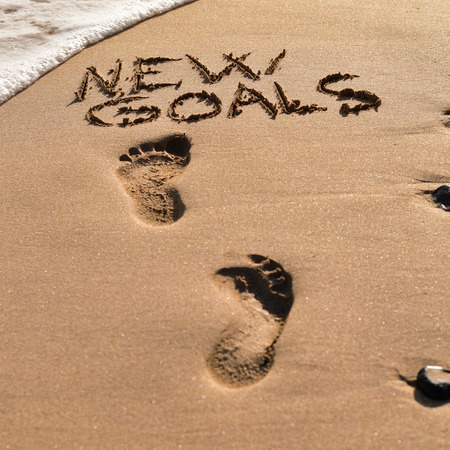 new beginnings: some foot prints and the text new goals written in the sand of a beach