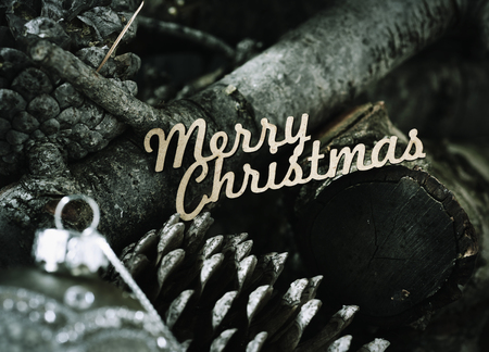 homelike: the text merry christmas on a pile of dry branches and pine cones, and a christmas ball in the foreground