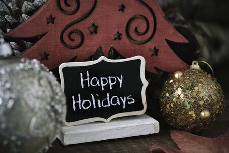 homelike: some christmas balls and a black signboard with the text happy holidays written in it, next to a wooden christmas tree and some pine cones Stock Photo