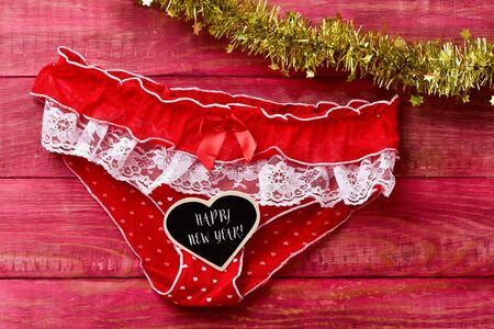 red panties and text happy new year written in a heart-shaped signboard, on a rustic red wooden background ornamented with golden tinsel Stock Photo