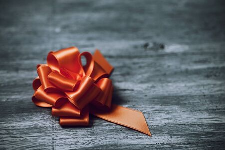 loopy: an orange satin gift ribbon bow on a rustic wooden surface, with a negative space