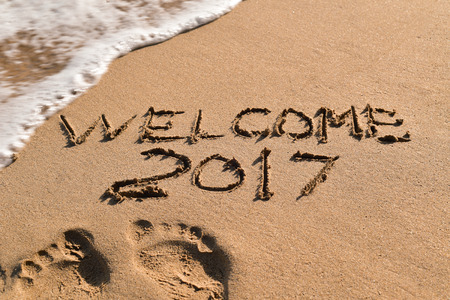 seven years: some foot prints and the text welcome 2017 written in the sand of a beach