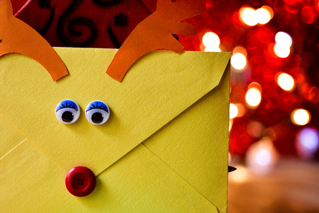 closeup of an envelope customized as a reindeer face with a button as nose and paperboard antlers, containing a letter to santa, placed next to a wooden christmas tree