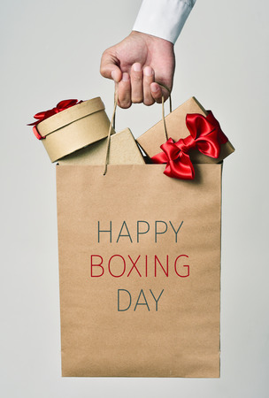 boxing day: closeup of the hand of a young caucasian man holding a paper shopping bag full of gifts and the text happy boxing day written in it Stock Photo