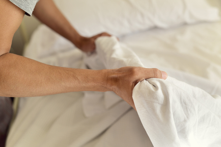 bedlinen: closeup of a young man extending the bedsheet or the duvet on the mattress as he is making the bed