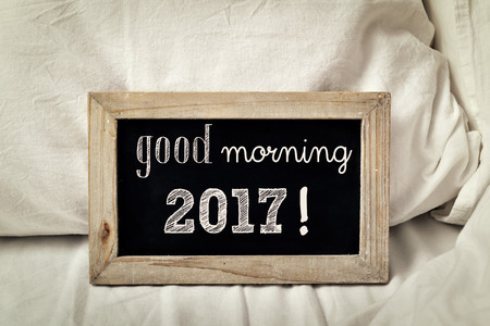 bedlinen: a wooden-framed chalkboard with the text good morning 2017 written in it, placed on a bed set with white bedlinen Stock Photo