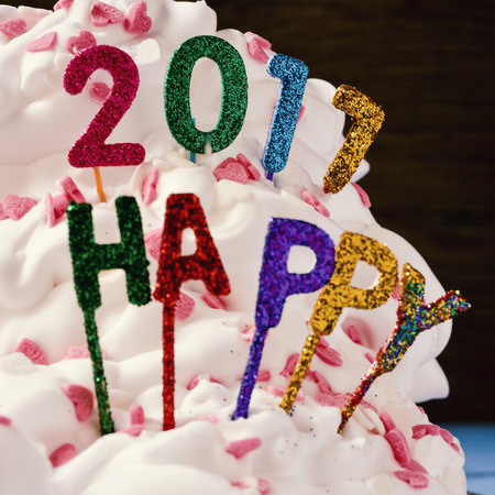sweet seventeen: closeup of some glittering letters and numbers of different colors forming the text happy 2017, topping a cake