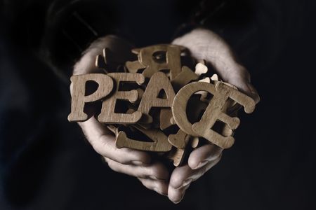 closeup of an old caucasian man holding a pile of wooden letters in his hands, some of them forming the word peace