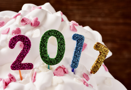 sweet seventeen: closeup of four glittering numbers of different colors forming the number 2017, as the new year, topping a cake Stock Photo