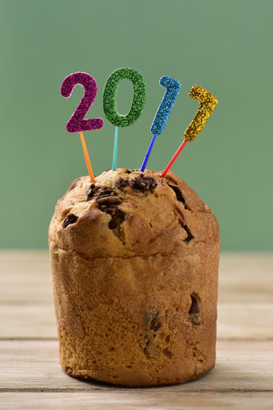 closeup of four glittering numbers of different colors forming the number 2017, as the new year, topping a cake Stock Photo