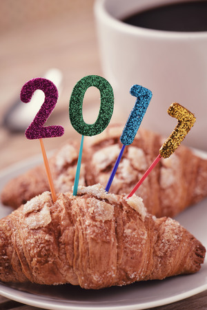 sweet seventeen: closeup of four glittering numbers of different colors forming the number 2017, as the new year, topping a small croissant and a cup of coffee placed on a table set for breakfast Stock Photo