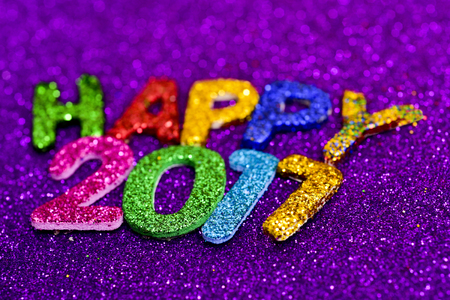 closeup of some glittering letters of different colors forming the text happy 2017, on a violet glittering background