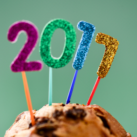sweet seventeen: closeup of four glittering numbers of different colors forming the number 2017, as the new year, topping a cake, against a blue background