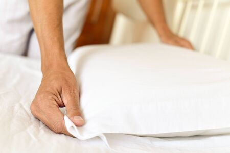 closeup of a young caucasian man arranging the pillow as he is making the bed