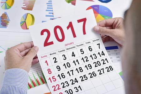 headman: a young caucasian businessman at his office desk full of charts observes a 2017 calendar