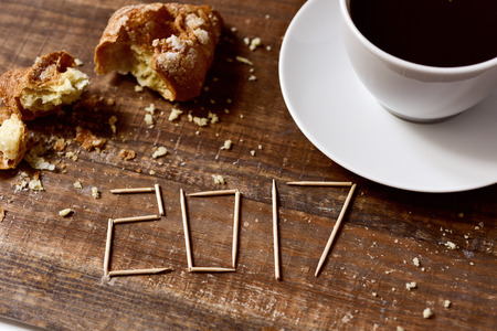 sweet seventeen: toothpicks forming the number 2017, as the new year, on a rustic wooden table or a wooden bar next to a cup of coffee and a smashed croissant Stock Photo