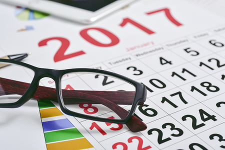 headman: closeup of a pair of eyeglasses and a 2017 calendar on an office desk full of charts