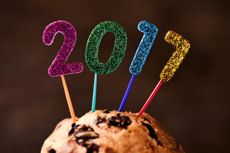 sweet seventeen: closeup of four glittering numbers of different colors forming the number 2017, as the new year, topping a cake, against a brown background