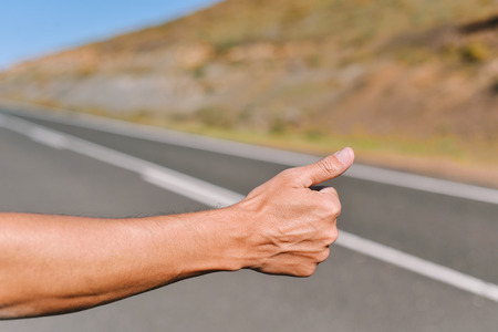 closeup of the hand of a young caucasian man hitchhiking in a minor road, with his thumb up