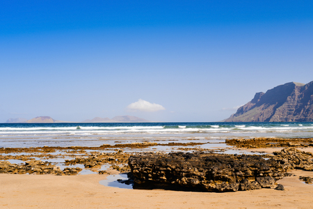 a view of the Famara Beach in Lanzarote, Canary Islands, Spain, with the Famara massif to the right and La Graciosa island in the background Stock Photo