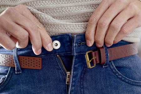 closeup of a young caucasian man trying to fasten his trousers, after his weight gain Stockfoto